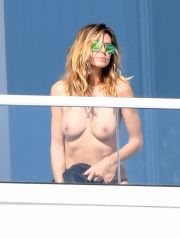 EXCLSUIVE, £500 MINIMUM FEE APPLIES, Miami, Florida - Supermodel Heidi Klum sunbathes topless on her balcony and peers over to watch her boyfriend Vito Schnabel go for a dip down on the beach. After his swim, Vito then joined Heidi on the balcony. 