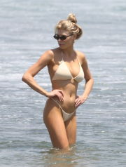 Malibu, CA  - *EXCLUSIVE*  - Charlotte McKinney beats the heat by taking a dip in the ocean. Charlotte shows off her bikini body with her hair in an updo, gold hoop earrings, sunglasses, and an off white bikini as she enjoys the dip with a friend.